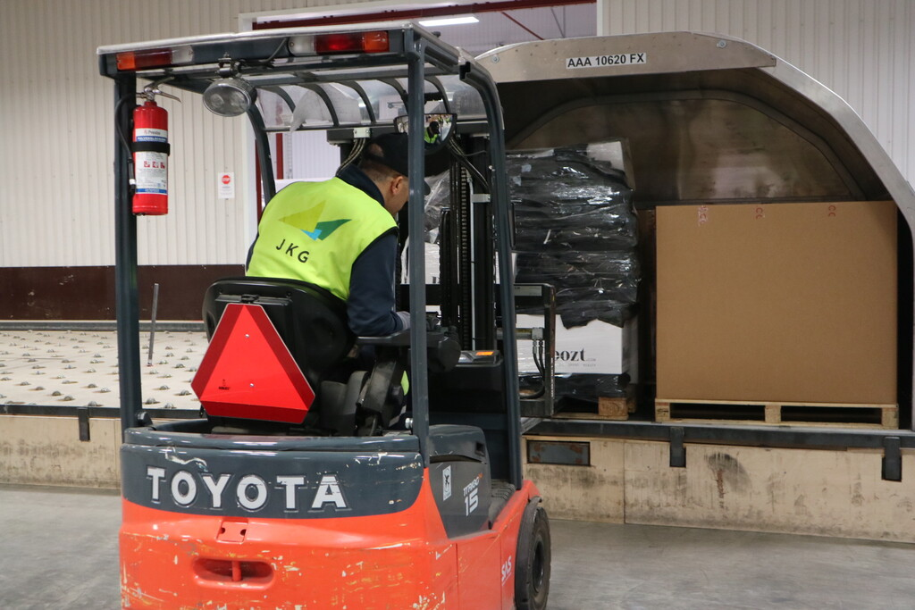 Employees move goods by truck in the freight terminal